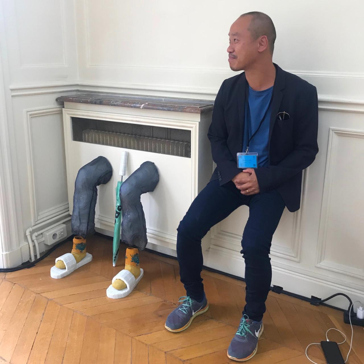 Gallerist Joseph Tang showing empathy for a sculpture by Adam Cruces & Louisa Gagliardi
